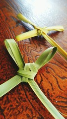 Close-up Of Palm Crosses On Wooden Table