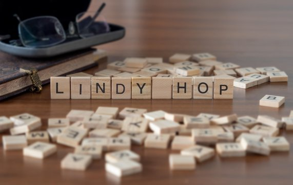 lindy hop dance style concept represented by wooden letter tiles on a wooden table with glasses and a book