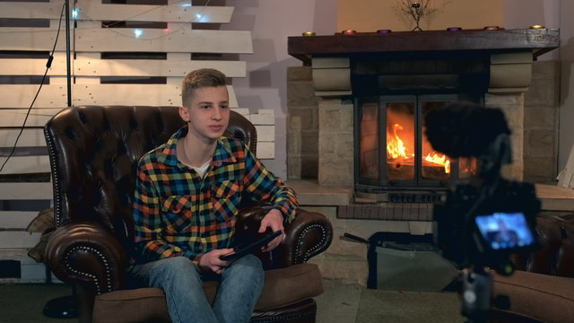 Home video shooting: teenage boy speaking something to camera with tablet in his hands. He sitting in comfortable leather armchair near the fireplace