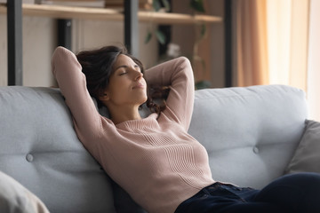 Carefree young beautiful housewife mother napping on couch alone at home. Peaceful millennial caucasian woman relaxing on comfortable sofa, enjoying free leisure vacation weekend time in living room.