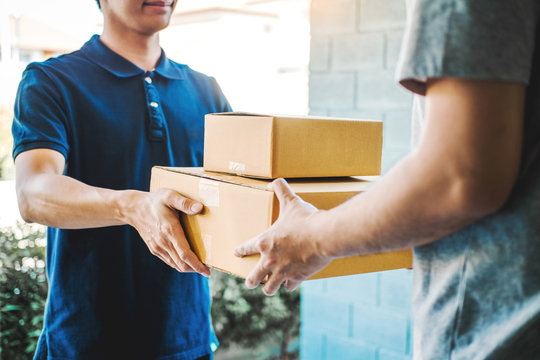 Delivery concept Asian Man hand accepting a delivery boxes from professional deliveryman at home