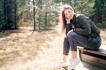 A young happy woman sitting on a wooden bench in the forest or a park and smiling looking directly into the camera.