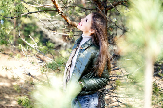 A young stylish woman standing next to a pine tree in a forest or in a park and smiling and looking in an upward direction.