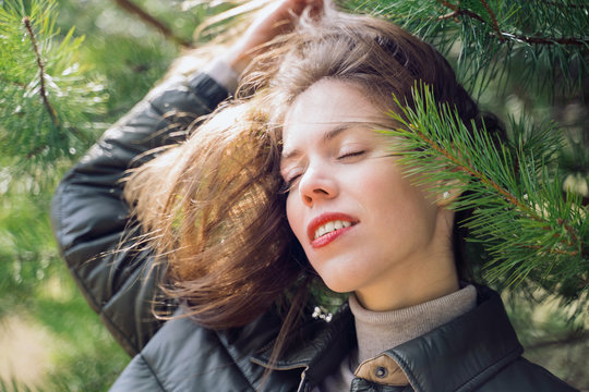 A portrait of a young woman surrounded by foliage. A concept of relaxation in nature.