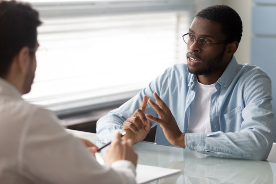 Serious african american candidate talking with businessman at job interview in office. Businessman manager listening client, good business partners negotiation.