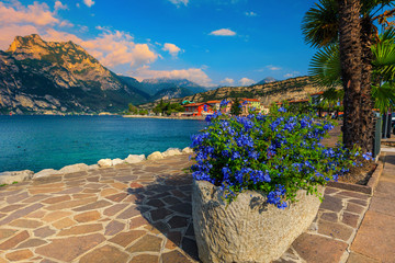 Wall Mural - Walkway decorated with flowers on the waterfront, lake Garda, Italy