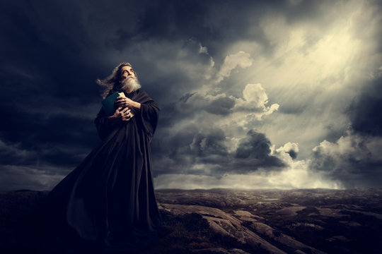 Monk Holding Bible Looking Up to God Sky Light, Old Priest in Black Robe in Storm Mountains
