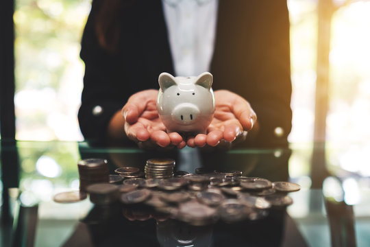Closeup image of a businesswoman holding piggy bank with pile of coins on the table for saving money and financial concept