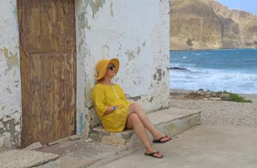 Papier Peint - mujer con sombrereo amarillo y vestido amarillo sentada casa playa mediterraneo almería  4M0A6627-as20