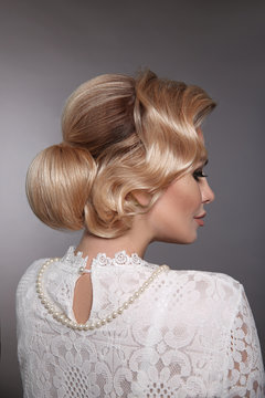 Wedding hairstyle. Portrait of Retro woman with shiny wavy bundle hair, feather in head. Back view of Elegant lady posing isolated on studio grey background. Beautiful blonde bride.