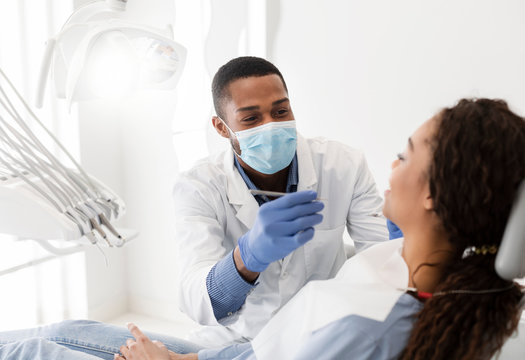 African american dentist making treatment in modern clinic