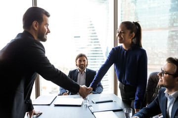 Smiling friendly businesswoman hr manager greeting candidate at meeting, shaking hand, congratulating successful applicant with getting job, business partners handshaking, celebrating deal