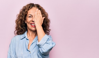 Wall Mural - Middle age beautiful woman wearing casual denim shirt standing over pink background covering one eye with hand, confident smile on face and surprise emotion.