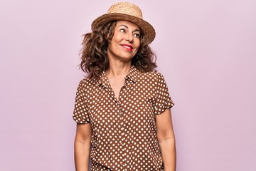 Wall Mural - Middle age beautiful woman wearing casual shirt and hat over isolated pink background looking to side, relax profile pose with natural face and confident smile.
