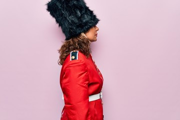 Wall Mural - Middle age beautiful wales guard woman wearing traditional uniform over pink background looking to side, relax profile pose with natural face with confident smile.