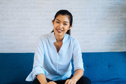 Happy friendly Asian woman looking at camera and talking, making video call conference, online job interview at home. Millennial female internet teacher tutor and vlogger on the job.