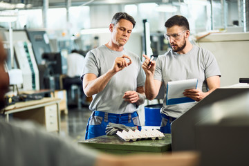 Factory workers examining finished products in industrial facility. Fotobehang