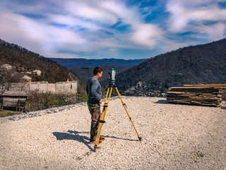Printed roller blinds Gray traffic A man with a total station. Surveyor man at work. Geodetic surveys during construction. Construction work on a sunny day. Set of total station and surveyor taking measurements at a construction site.
