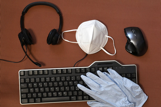 Smart working during Covid-19 or Coronavirus disease. Computer keyboard, mouse, headphone, gloves and protection mask ffp2 against covid-19 on a brown background.