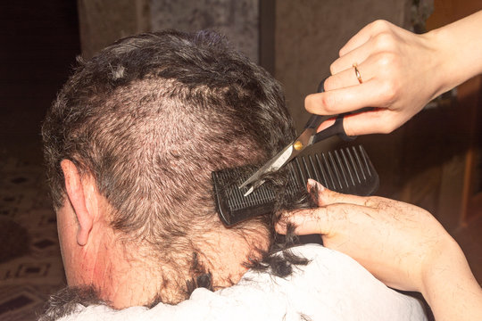 Men's haircut with scissors, poor hairdresser, improper haircut of black hair. Bad day at the hairdresser, inability, problem