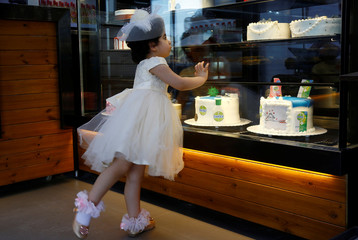 A girl looks at cakes with figures of Dettol bottles and models of the coronavirus, during the outbreak of the coronavirus disease (COVID-19),  at a cake shop in the holy city of Najaf
