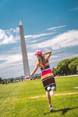 Wall Mural - Young sexy girl in a dress exploring Washington city near Washington monument on sunny day
