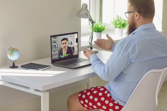 Online work at home. Funny fat businessman in red shorts works communicates video chat call using laptop in the room.
