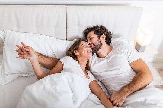 Happy couple is lying in bed together. Enjoying the company of each other.Happy young couple hugging and smiling while lying on the bed in a bedroom at home.