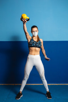 Young fit woman with n96 face mask  doing shoulder exersice at the gym with kettlebells. Fitness strength workout under coronavirus health crisis.