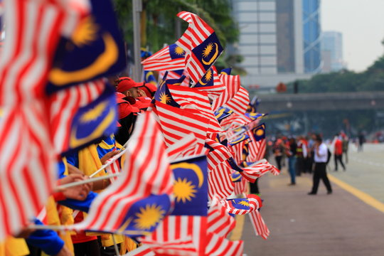 Group Of People Holding Malaysian Flag During Parade