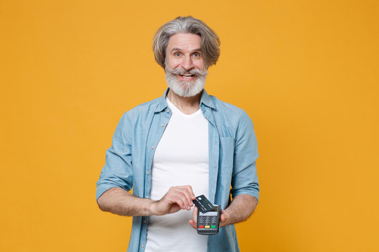 Cheerful elderly gray-haired mustache bearded man in blue shirt isolated on yellow background. People lifestyle concept. Hold modern bank payment terminal to process and acquire credit card payments.