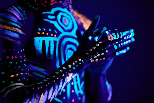 cropped photo of young male hands, UV body art glows. fantastic luminescent paint in neon light