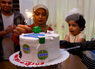 An Iraqi family celebrates their daughter's birthday with a cake with figures of Dettol bottles and models of the coronavirus, during the outbreak of the coronavirus disease (COVID-19), at a cake shop in the holy city of Najaf
