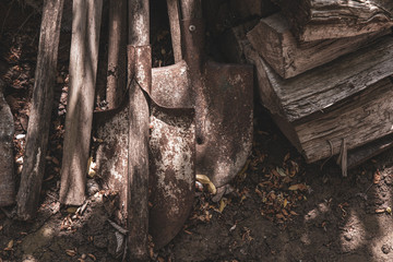 Old shovel in the ground. Farmhouse tools and firewoods on dirty ground. Rustic textures