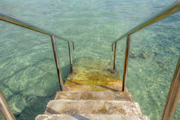 Inviting stairs leading into clear blue ocean water
