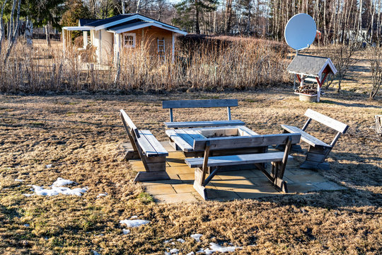 Stylish wooden barbeque spot with benches and table standing at concrete plates in the middle of backyard, spot of snow left at faded after winter grass. Small well and satellite dish at background