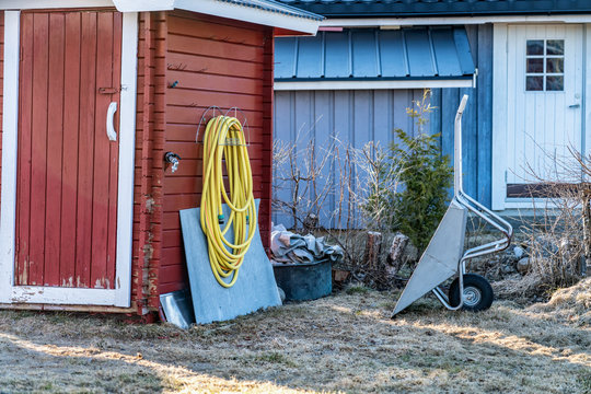 Yellow rubber watering tube for plants watering hangs on red wooden wall of traditional Swedish garden shed close to wall mounted water tap. Grey wheelbarrow stands up right on faded grass