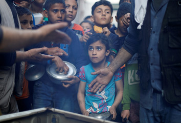 Palestinians wait to get soup offered for free during the Muslim fasting month of Ramadan in Gaza City