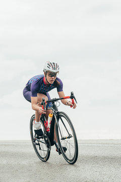 Isolated female road cyclist cycling fast