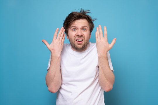 Hairy tired man on blue background. Guy does not like his hairstyle