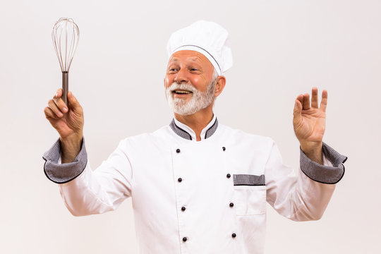 Image of  musical conductor senior chef with wire whisk on gray background.