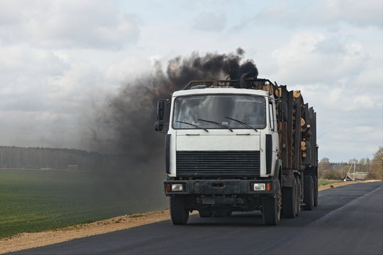Black smoke from the exhaust pipe of a diesel timber truck, harmful emissions from vehicles ecologe problem