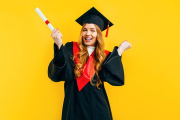 graduate girl with a diploma, shows a gesture of victory and success, on a yellow background.