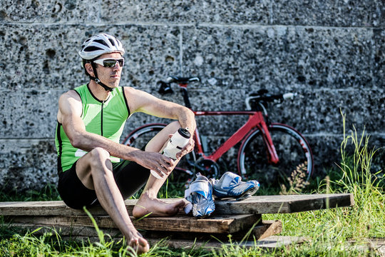 Cyclist Holding Water Bottle While Relaxing On Wooden Plank Against Wall
