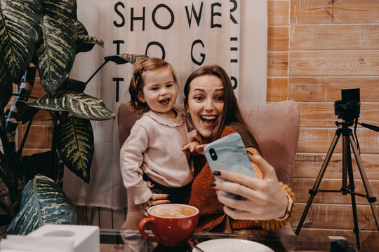 Online jobs for stay-at-home moms. Work From Home women with kids. Blogger girl and her little daughter have fun together. Young parenting blogger recording a video with her baby at home