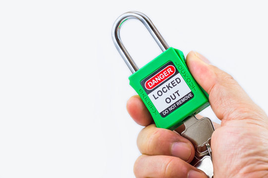 Hand holding green key lock and tag for process cut off electrical,the toggle tags number for electrical log out tag out on white background