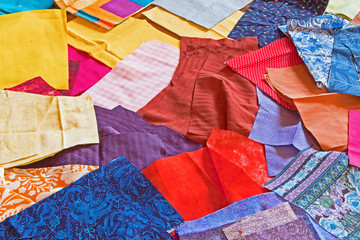 A patchwork of brightly colored cloth material is waiting to be sewn into homemade face masks.