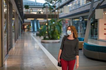 Erste Schritte einer jungen Frau mit Schutzmaske in die Öffentlichkeit nach Quarantäne während der Corona Pandemie