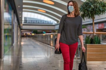Junge Frau mit Atemschutzmaske läuft durch ein leeres Einkaufszentrum