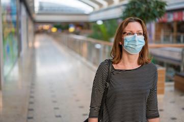 Frau läuft durch menschenleeres Einkaufszentrum während der Corona Krise